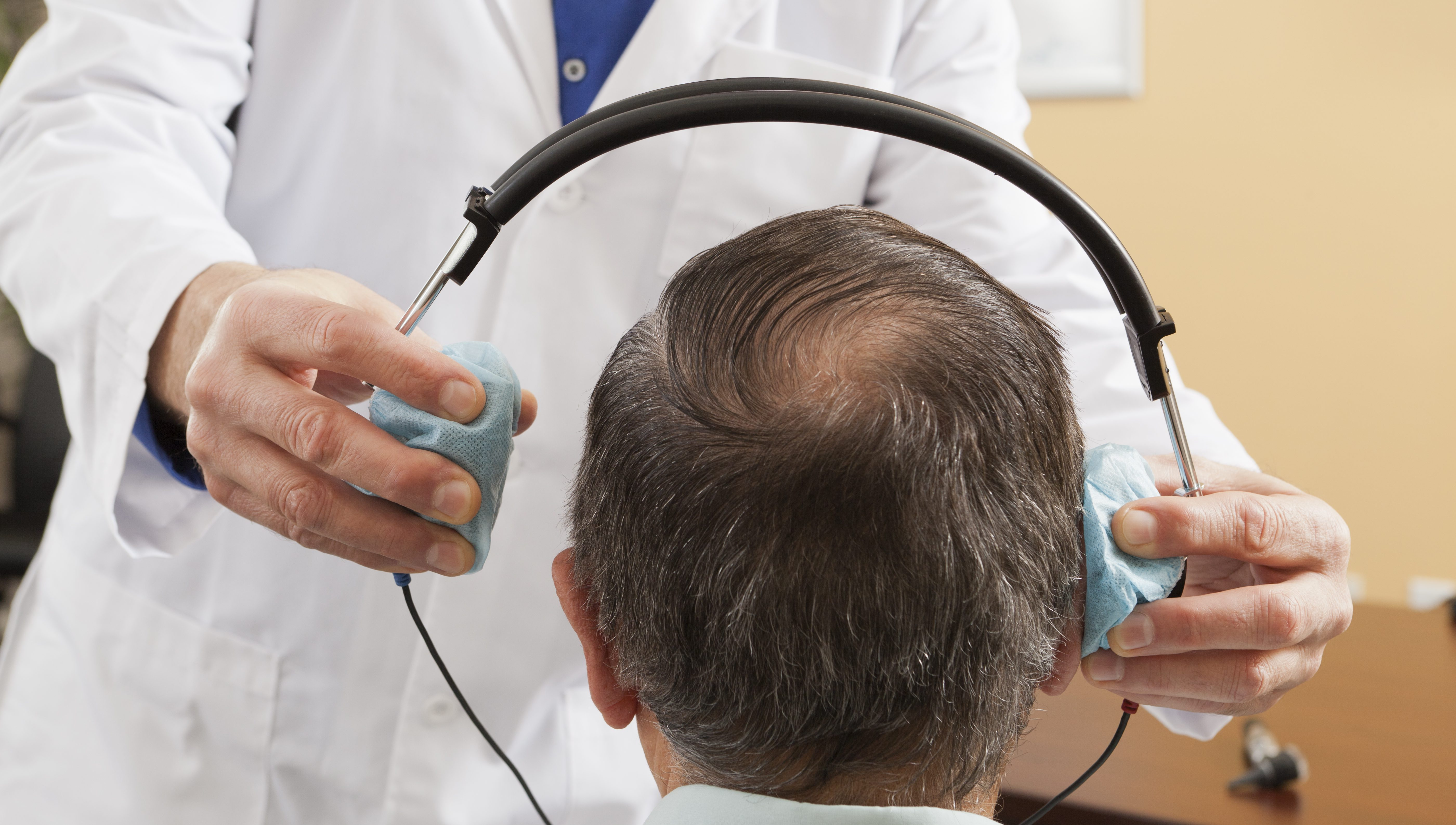 Audiologist placing a headset on a patient for audiometric evaluation