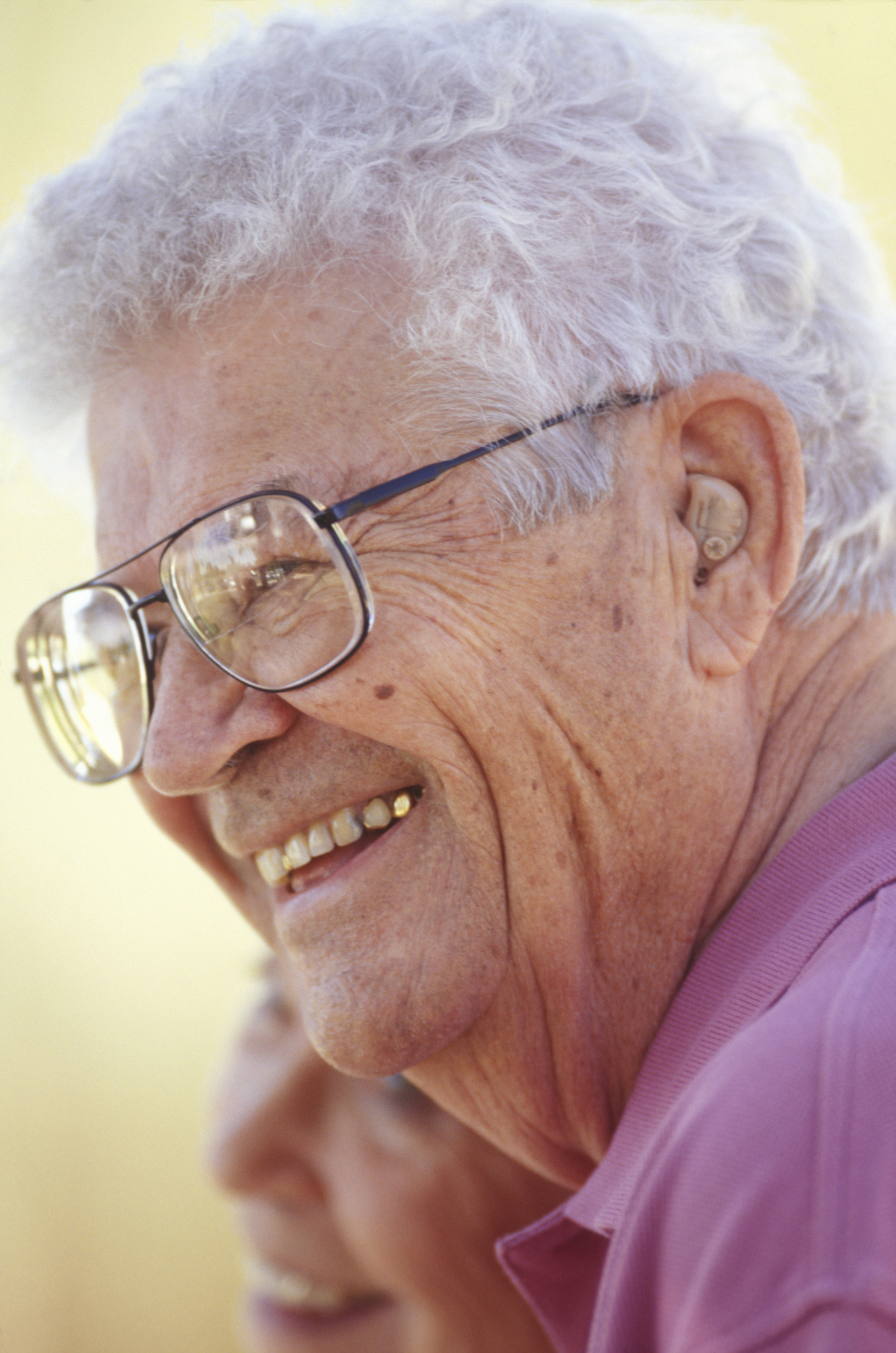Senior man wearing spectacles, smiling, outdoors, close-up