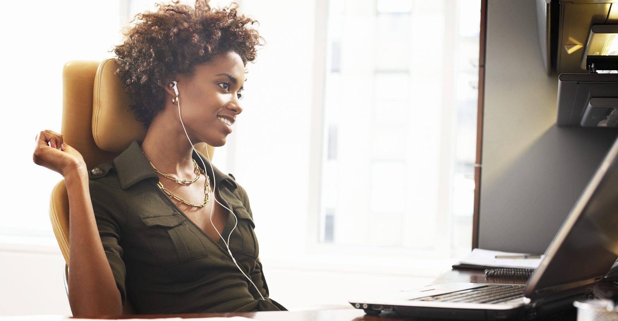 Businesswoman at desk wearing earphones, smiling