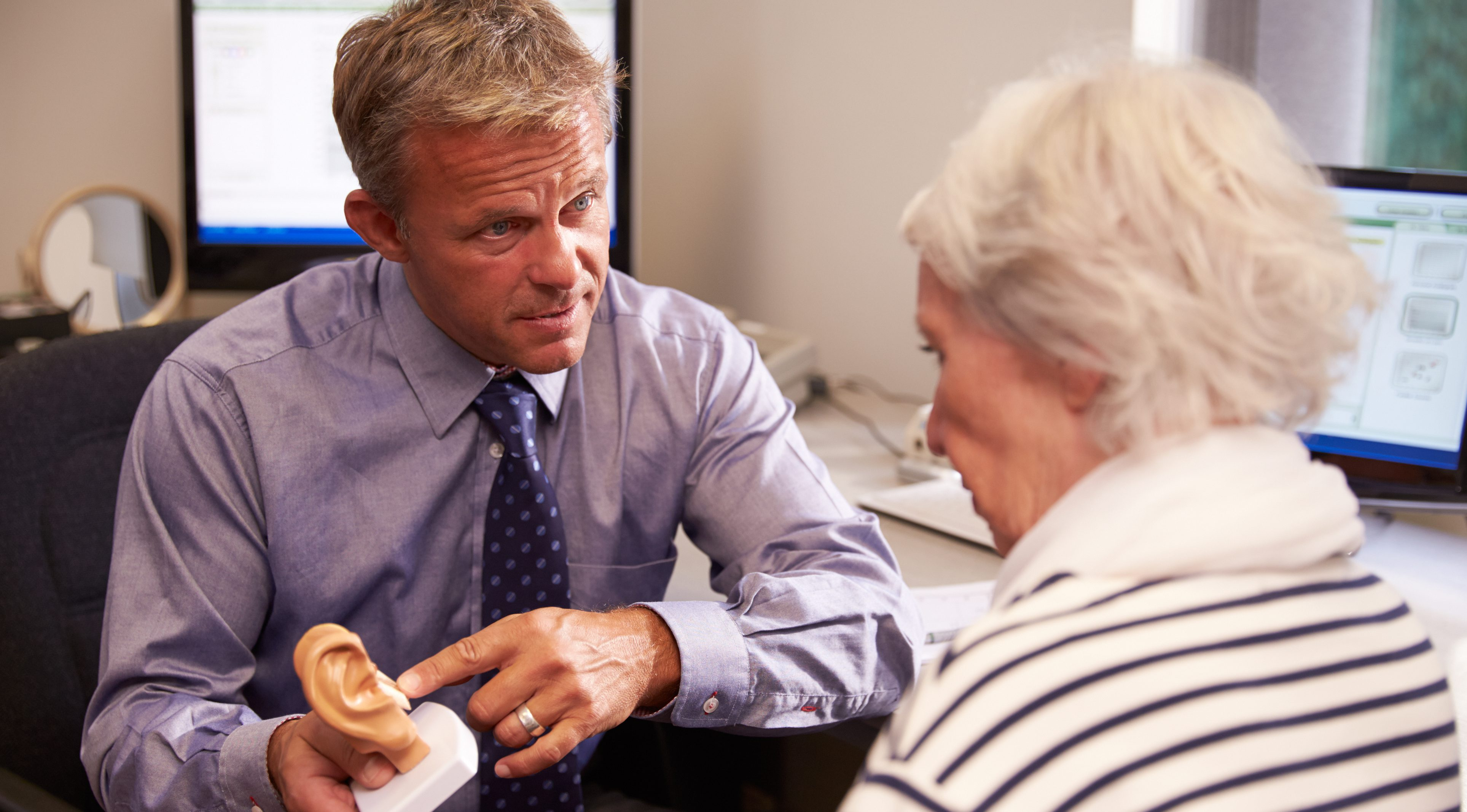 Doctor showing female patient a model of the human ear