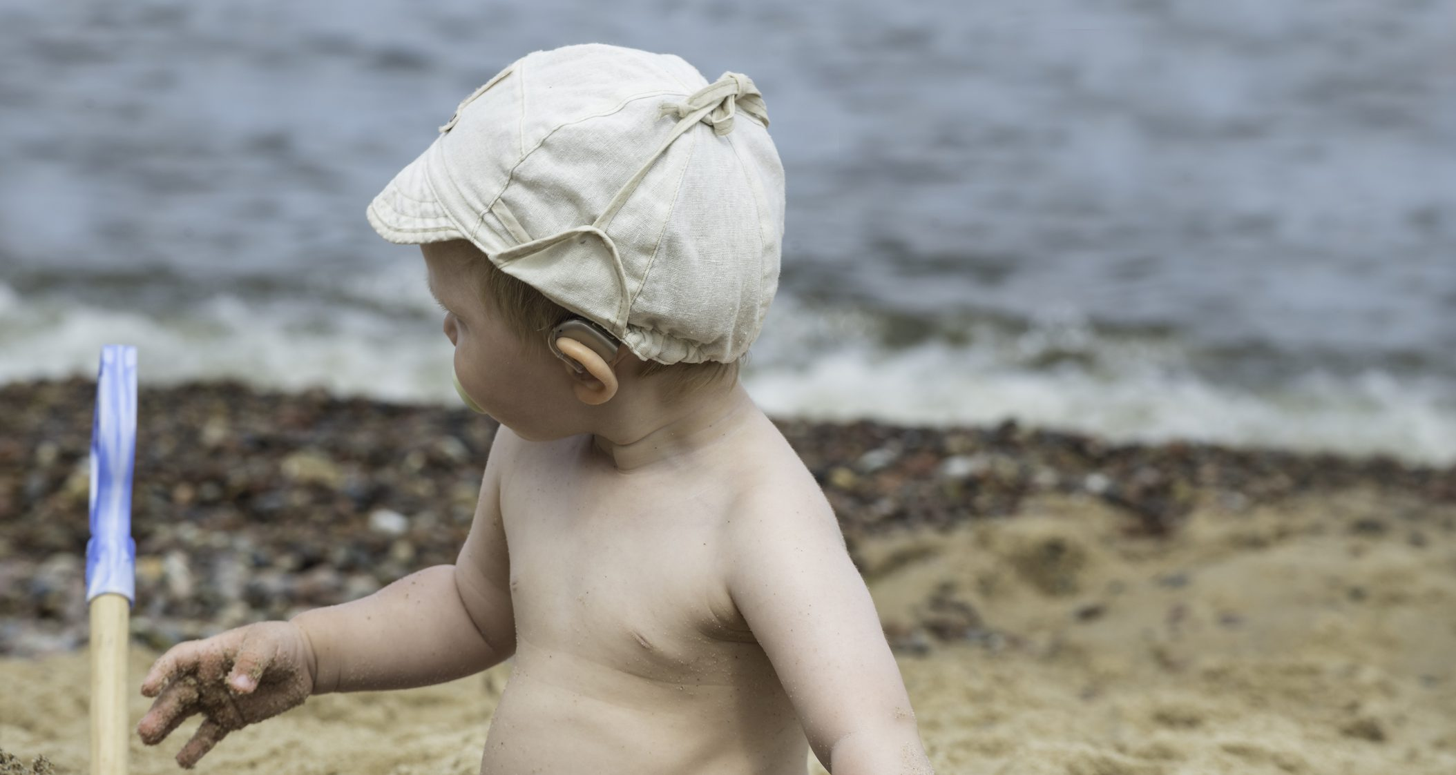 Baby with hearing aid looking at sea