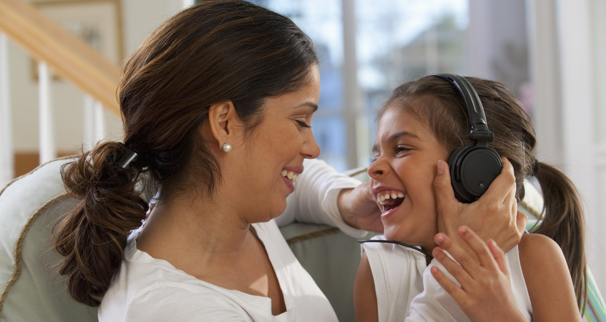 Hispanic girl sitting with her mother and listening to music