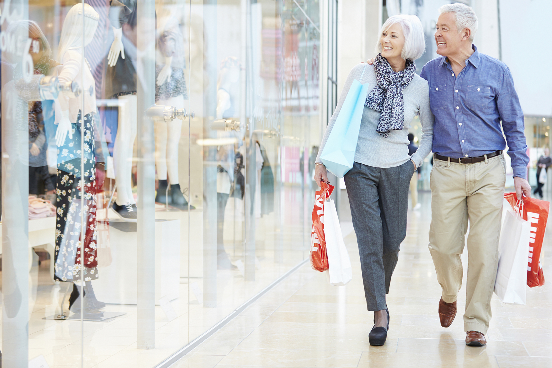 Happy Senior Couple Carrying Bags In Shopping Mall